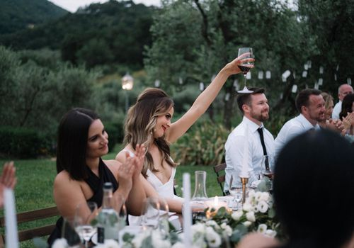 Bride holding up a glass of wine during a reception toast