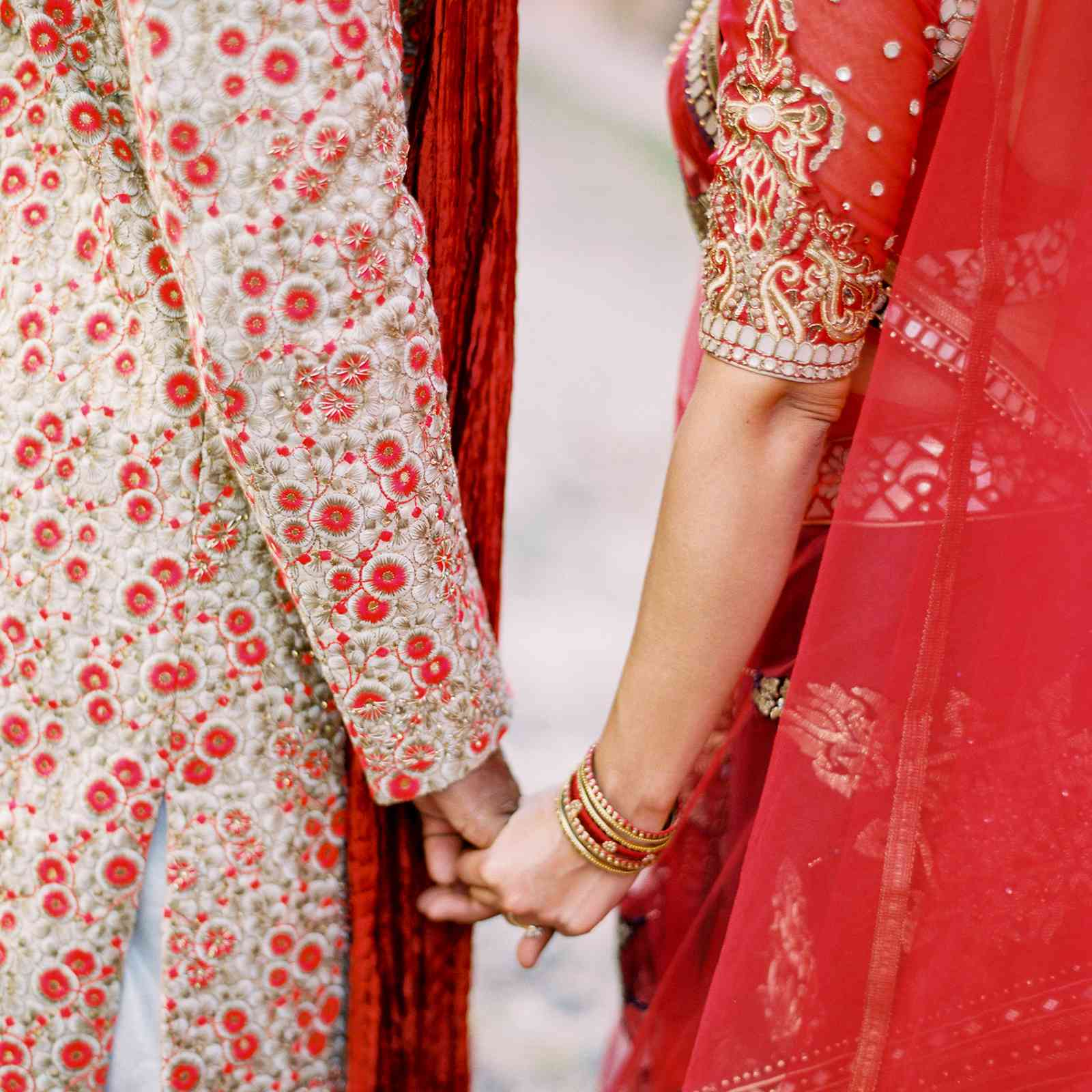 Bride and groom holding hands in traditional Indian attire