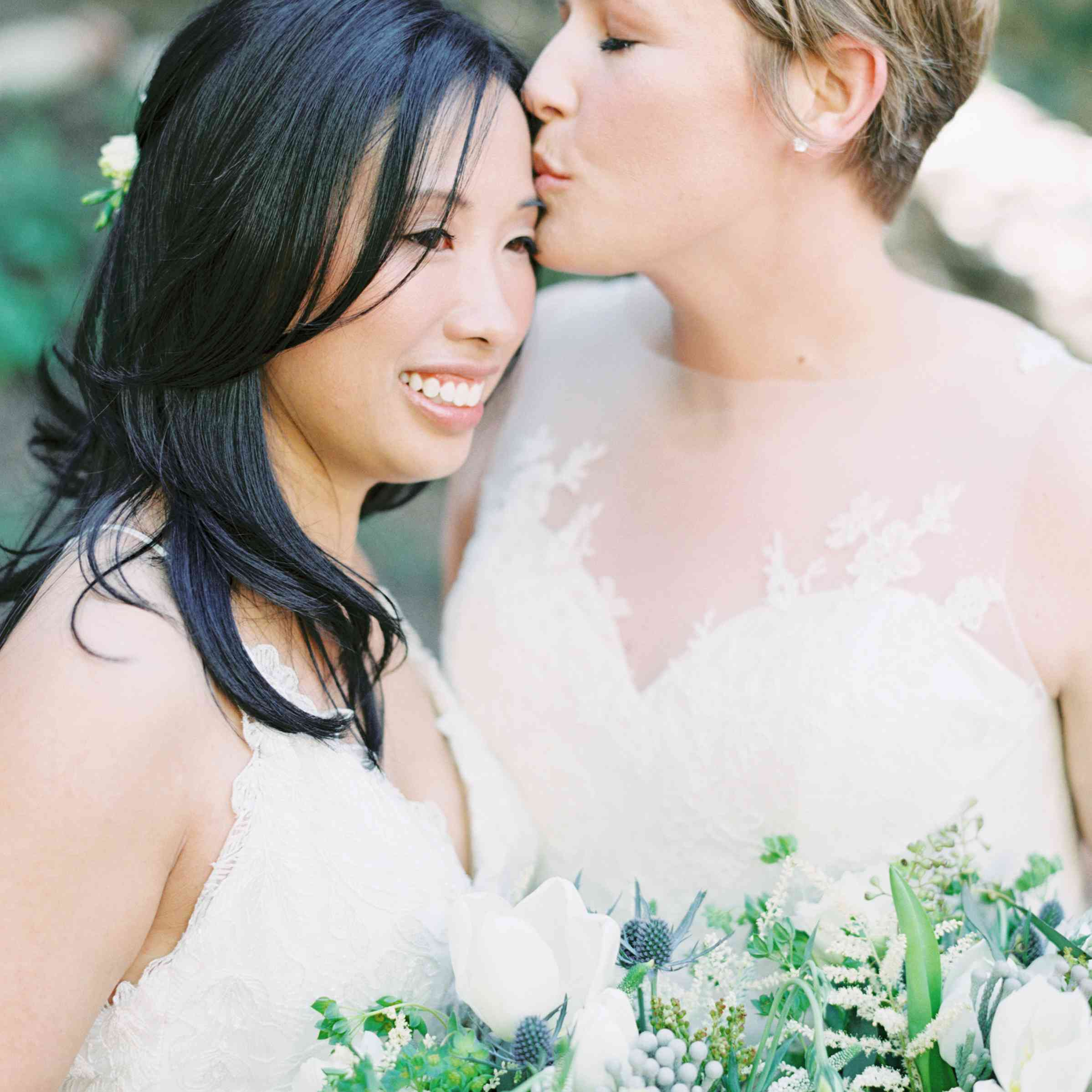 Bride kissing bride on the forehead