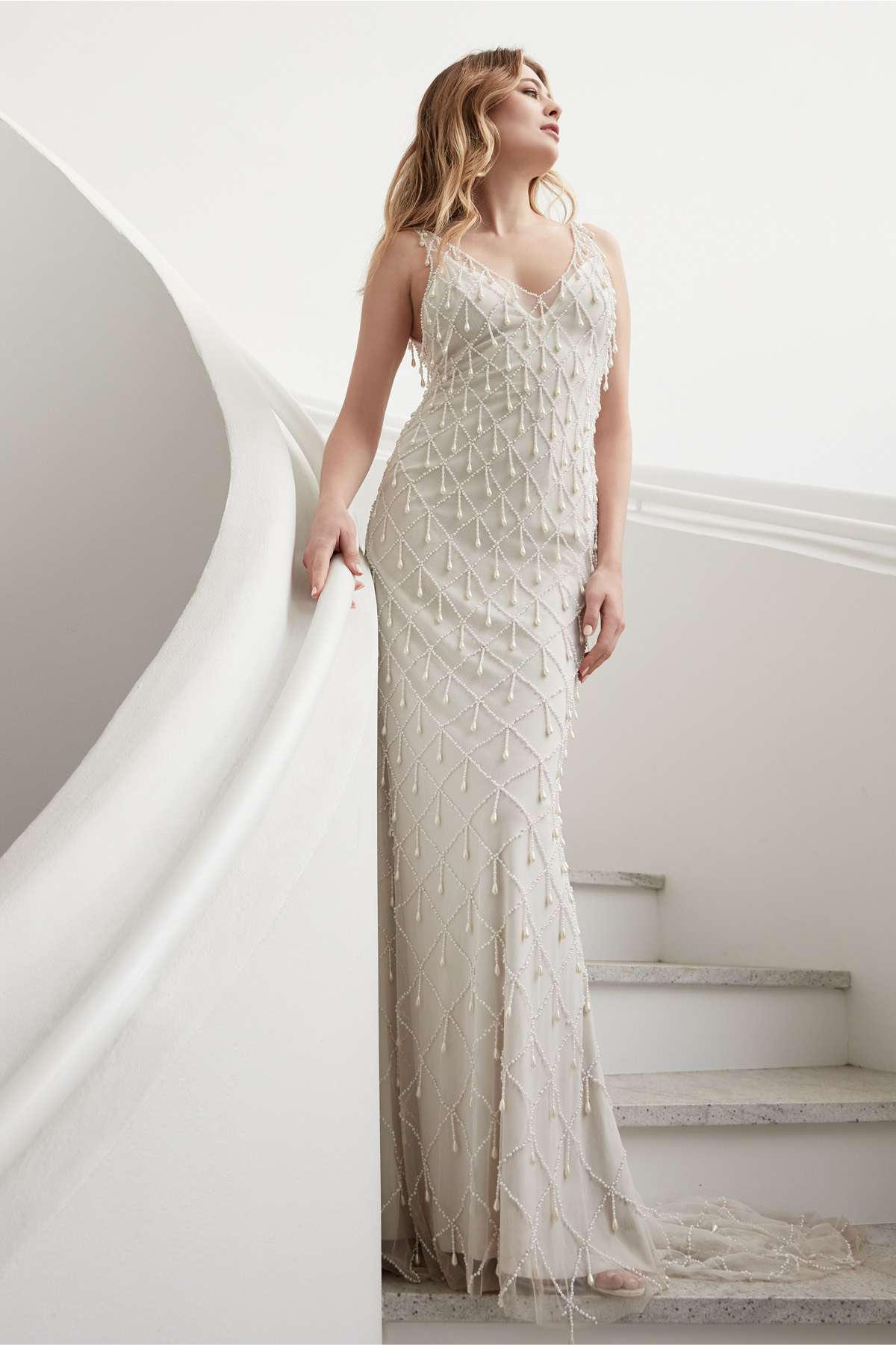 Model in sleeveless V-neck sheath dress with drop crystals in a lattice pattern