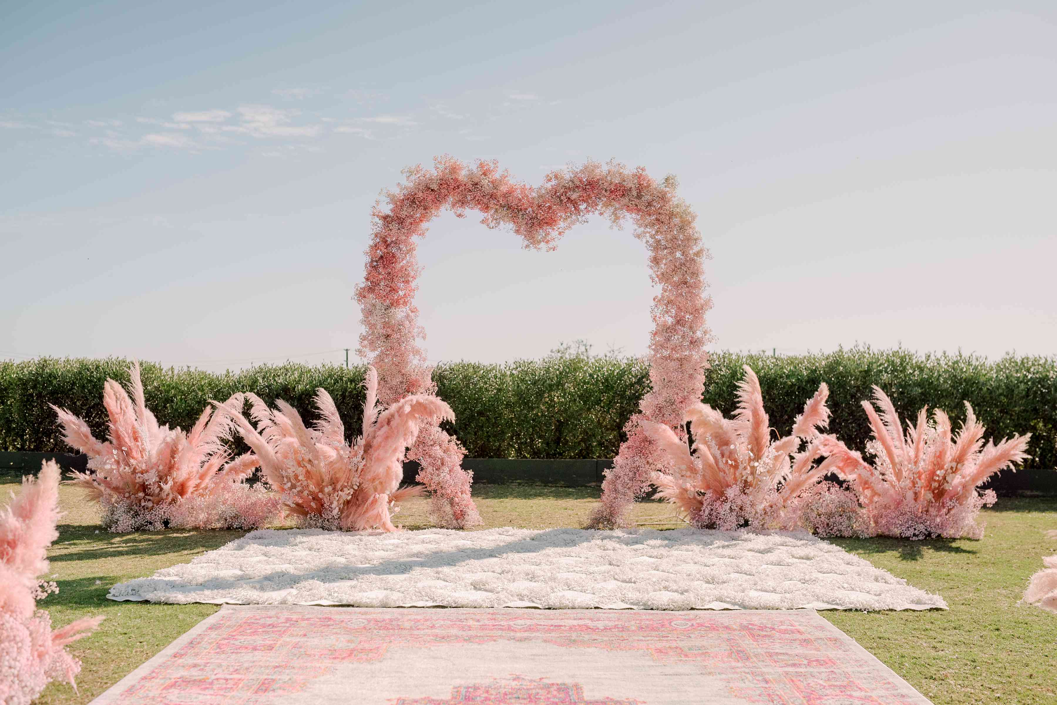 Pink floral heart-shaped ceremony arch surrounded by pink pampas grass