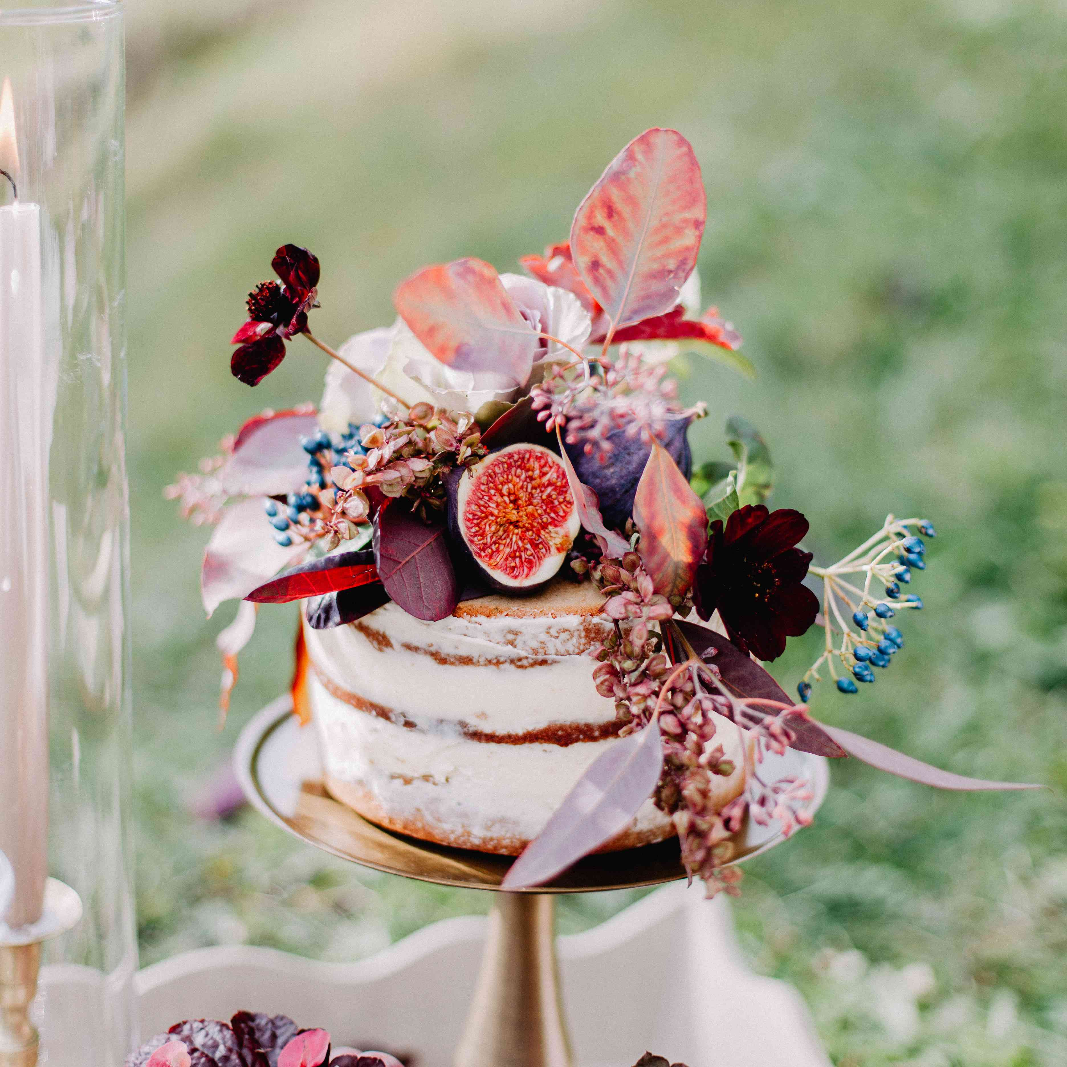 Semi-naked wedding cake with colorful fruit and floral accents