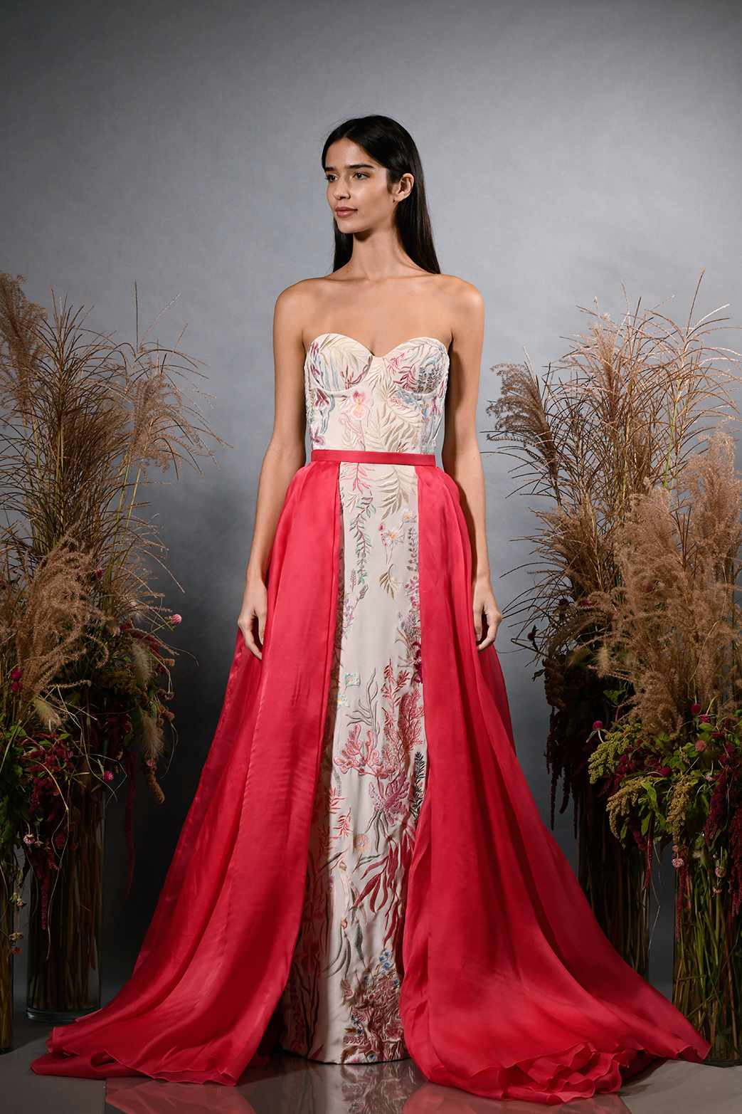 Model in strapless wedding dress with red overskirt