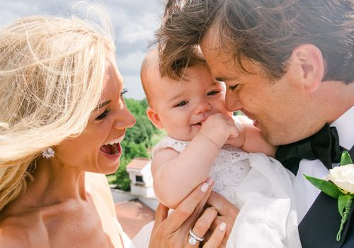 Bride and groom with baby main image