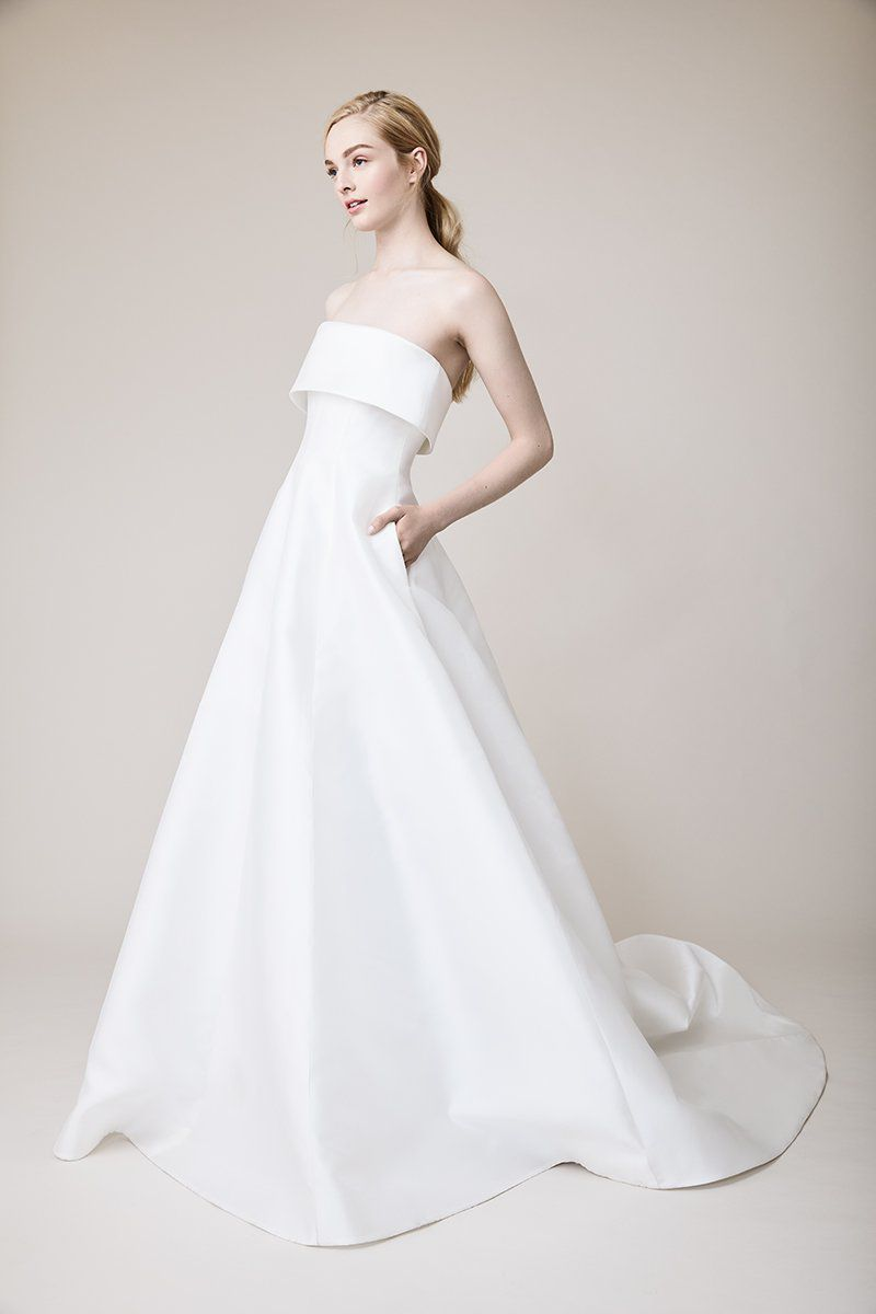 Model in strapless white gown with pockets