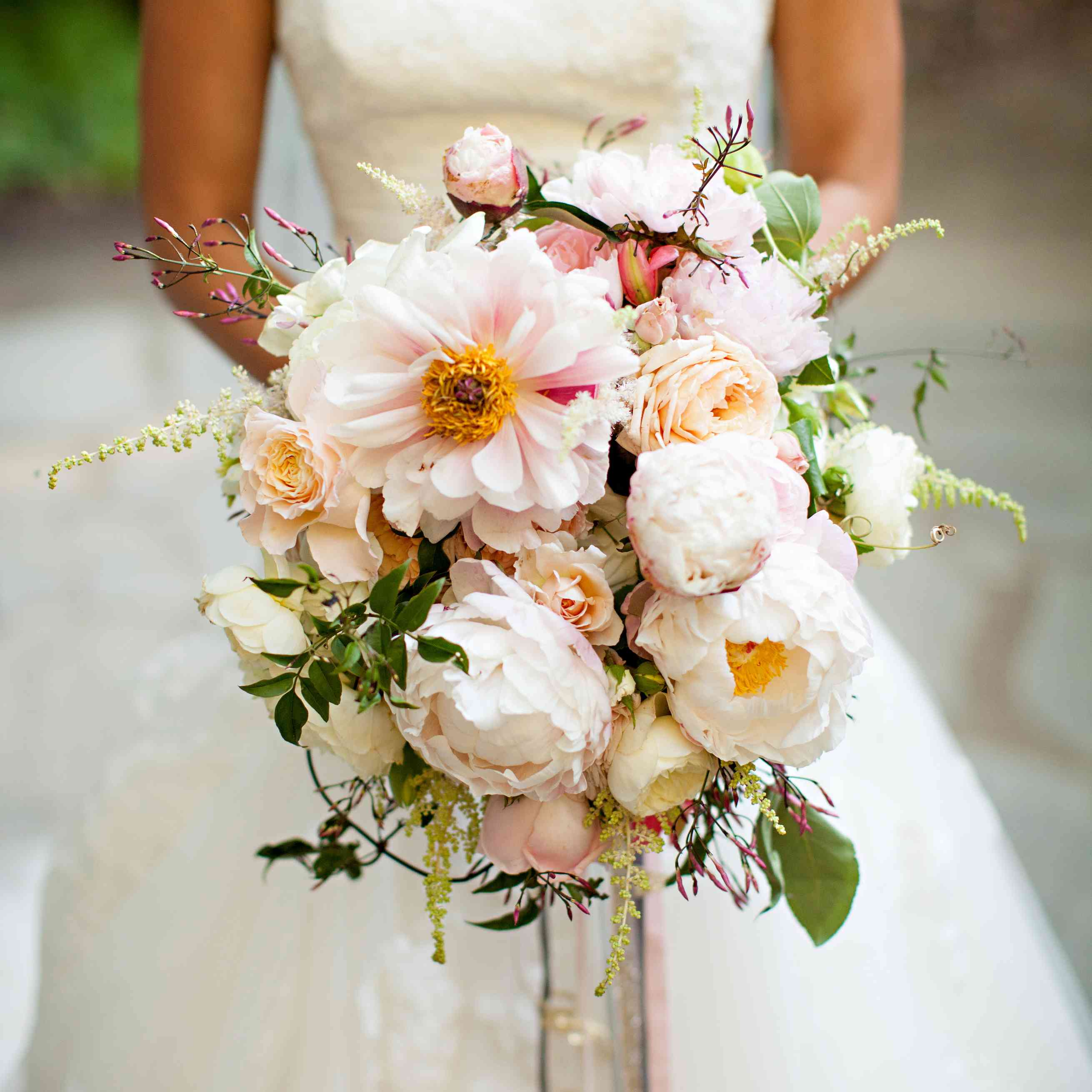 Bride holding a bouquet of jasmine, peonies, garden roses, and astilbe