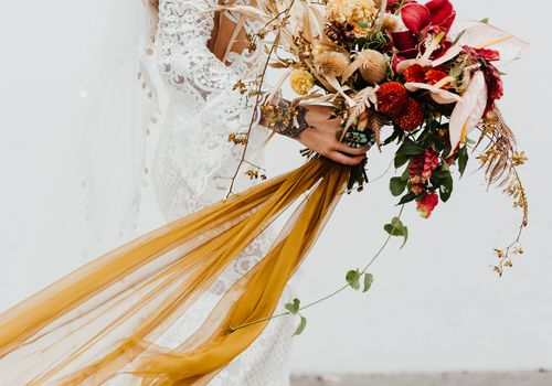 Bride holding a red and orange-gold bouquet