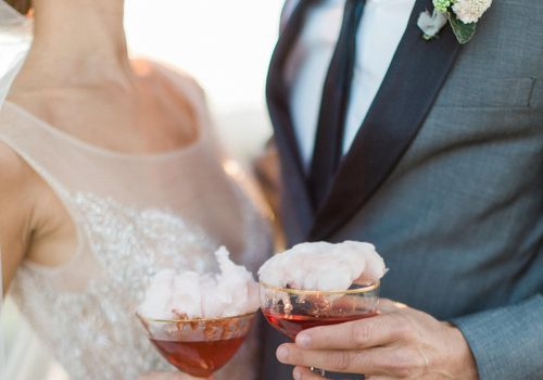 Couple holding a cocktail with cotton candy on top