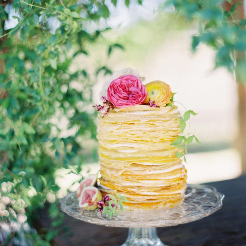 Yellow ruffled cake with floral topper