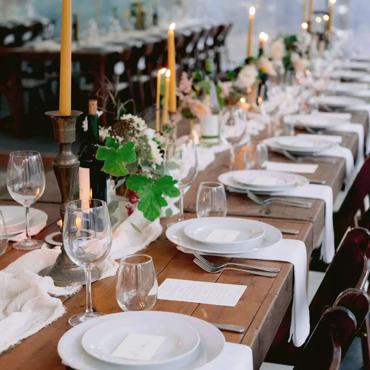 Long tables topped with handmade beeswax candles and greenery arrangements