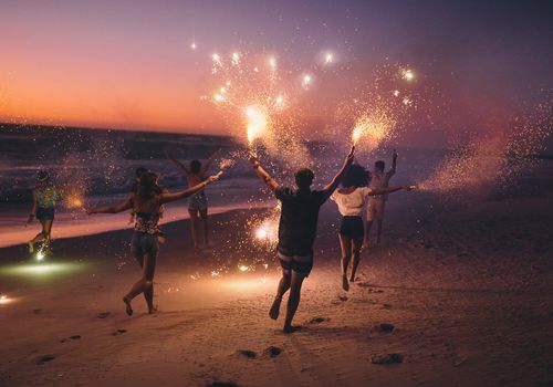 Friends running down the beach at sunset with sparklers