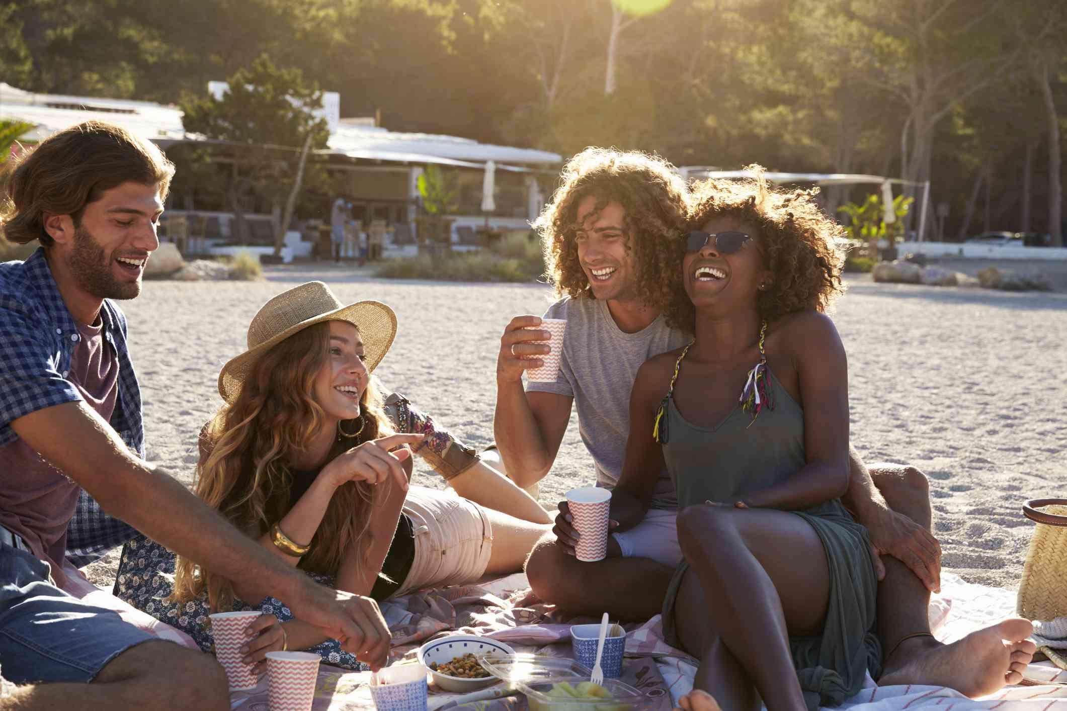 Four friends having a picnic on the beach