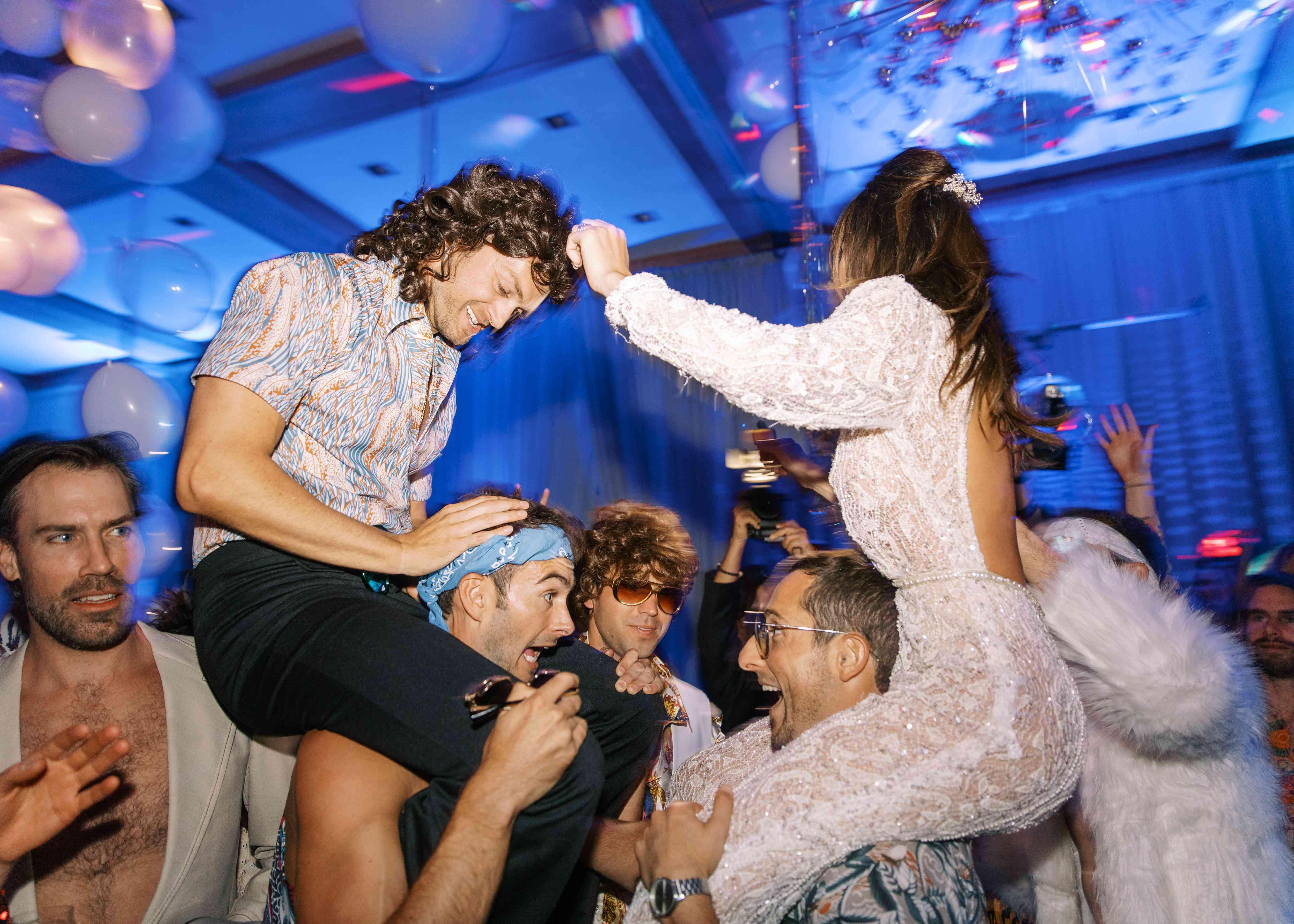 bride and groom on friends' shoulders