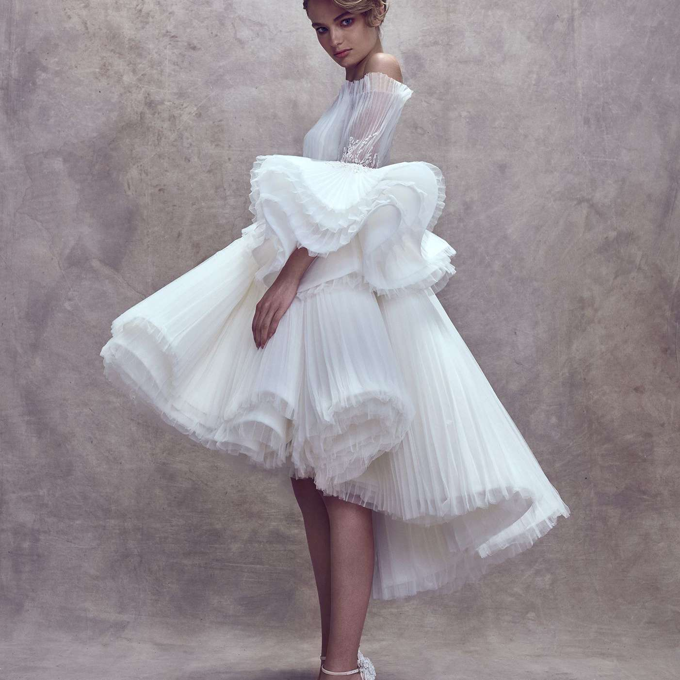 Model in off-the-shoulder dress with high-low layered tulle skirt and oversized sleeves