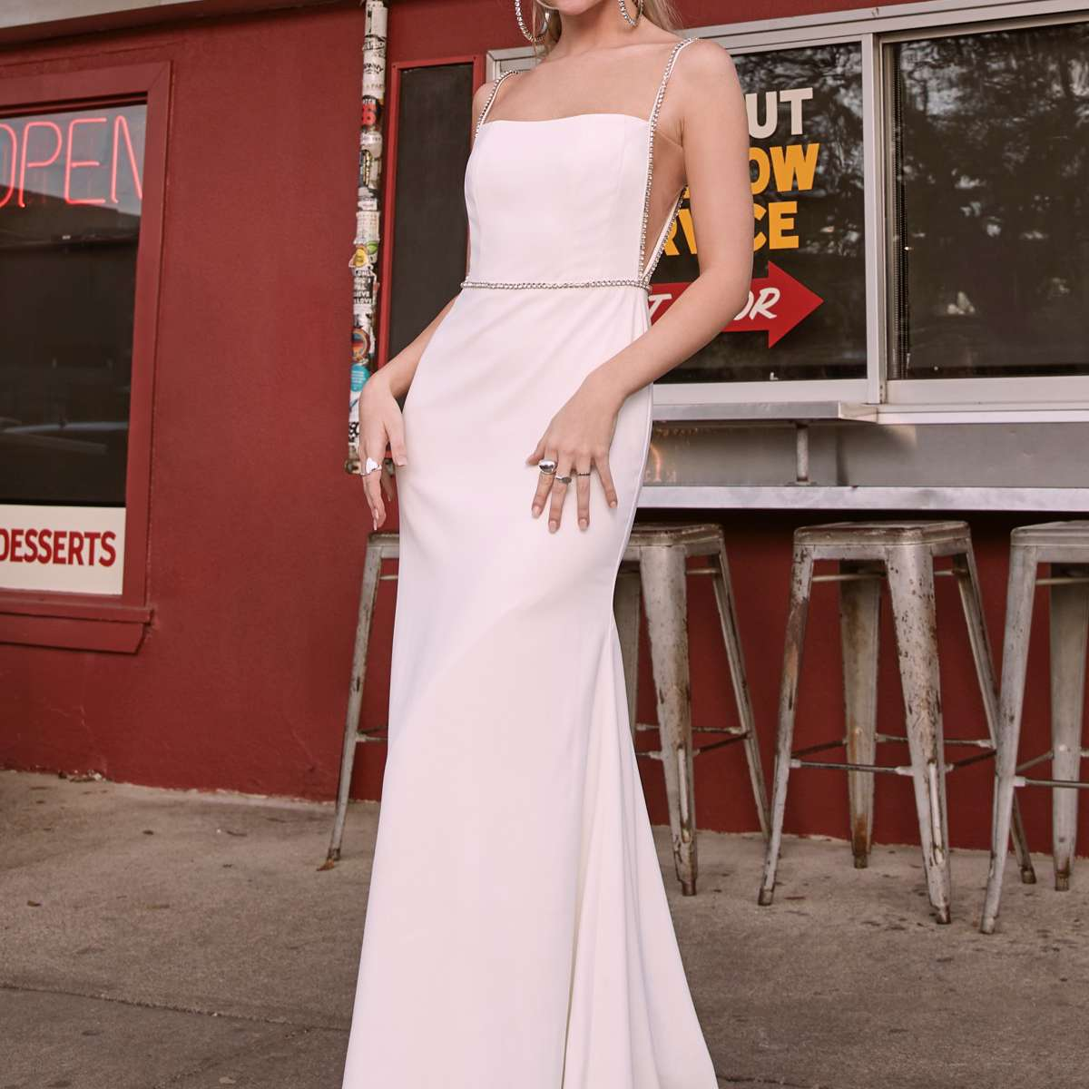 Model in fit-and-flare crepe gown with a square neckline and crystal straps and waistband