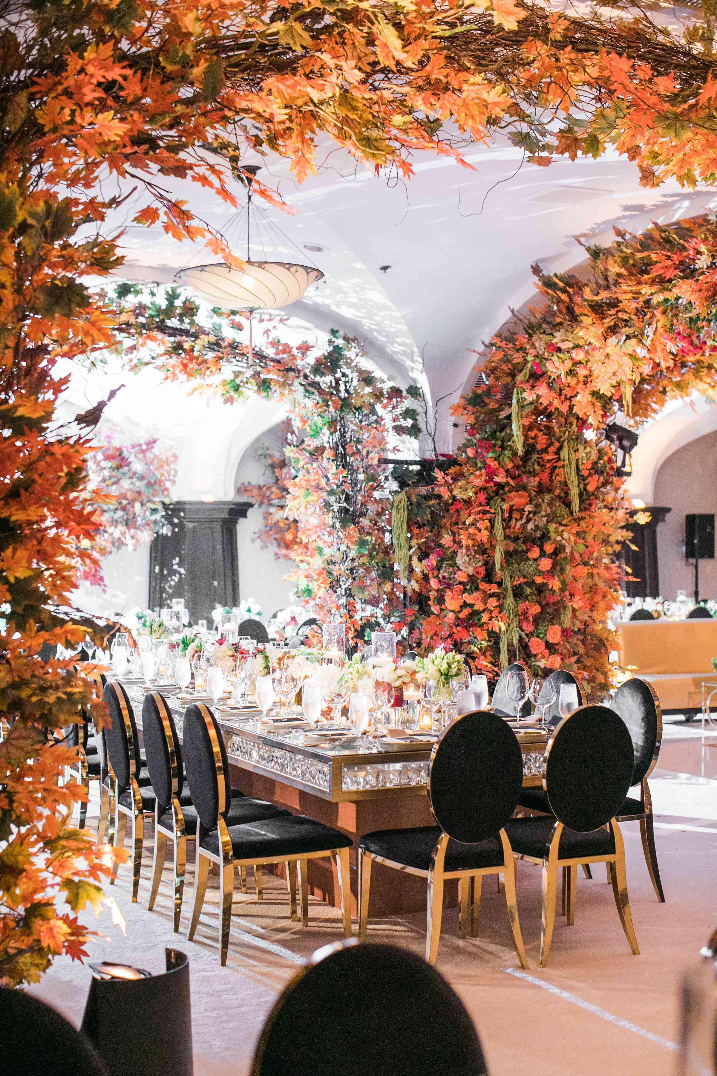 A reception venue with fall leaf arches