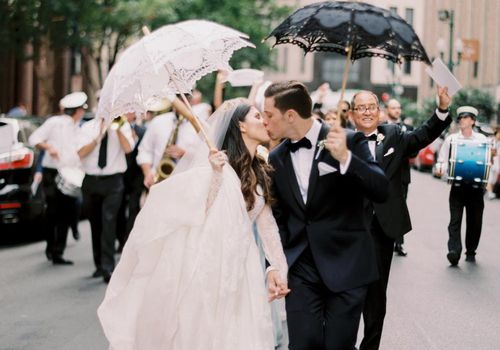 <p>Bride and groom carrying umbrellas</p>