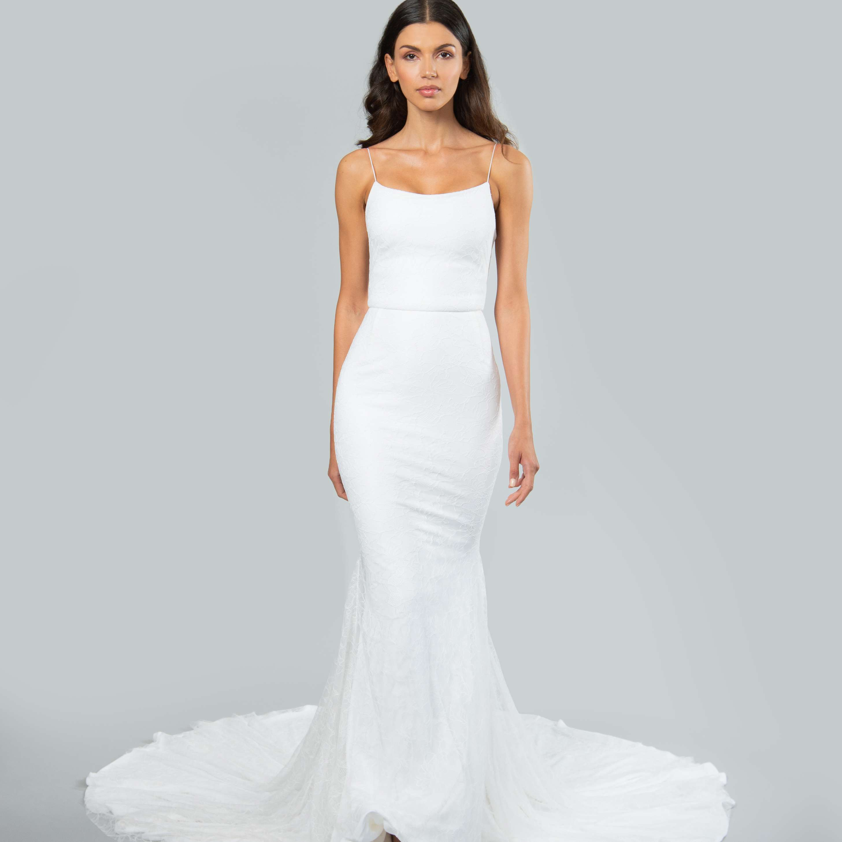 Model in fit-and-flare spaghetti strap wedding dress