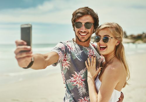Engaged couple taking selfie on beach