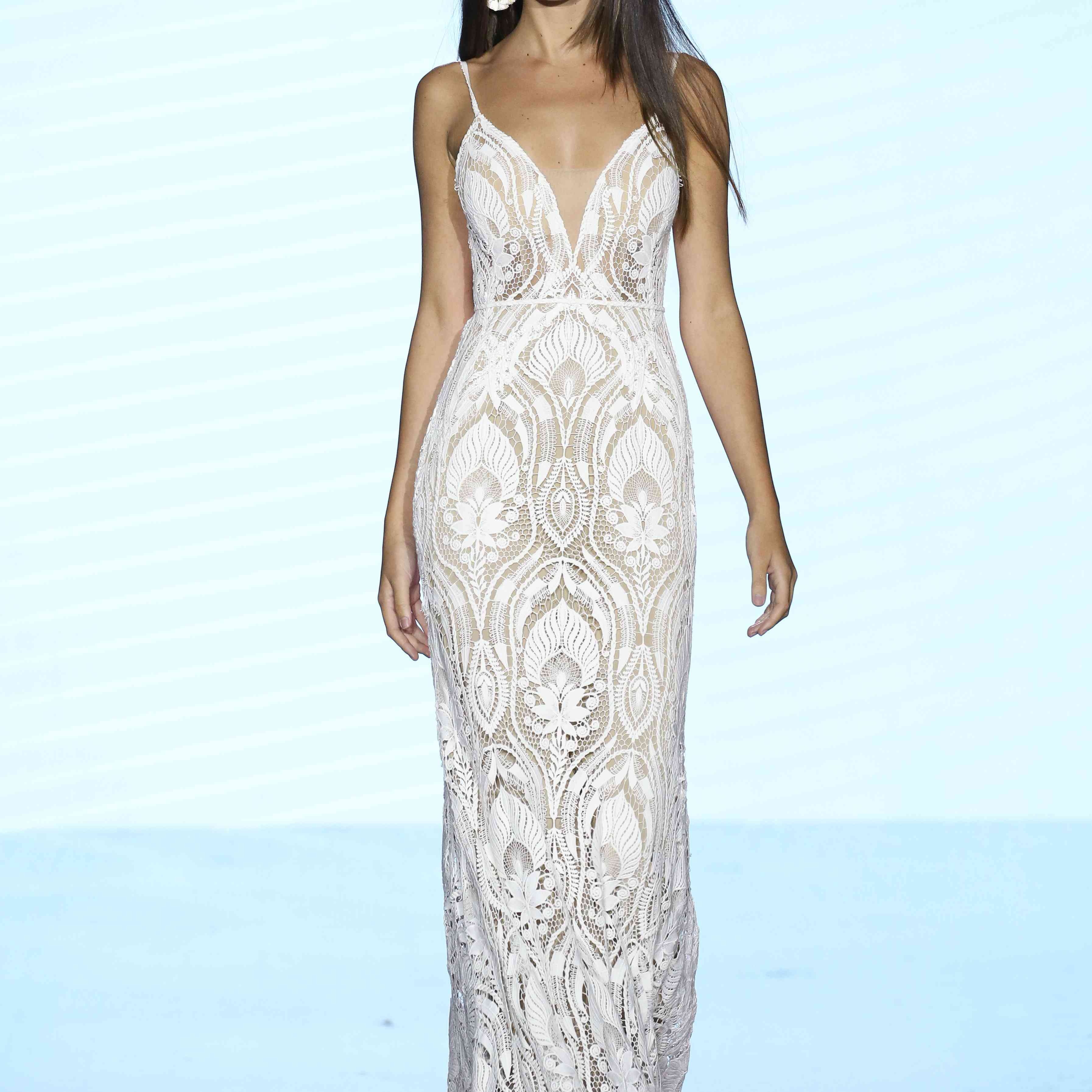 Model in fitted lace sheath gown with a plunging illusion neckline and spaghetti straps
