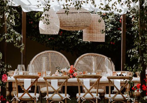 Rattan lanterns hanging above outdoor table