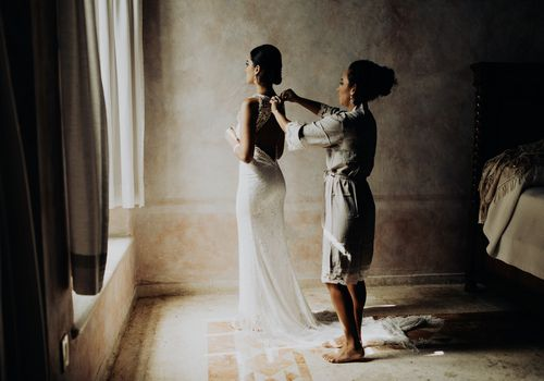 Mother helping the bride with top button of gown