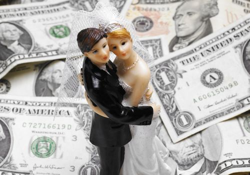 Bride and groom cake topper placed on a pile of dollar bills