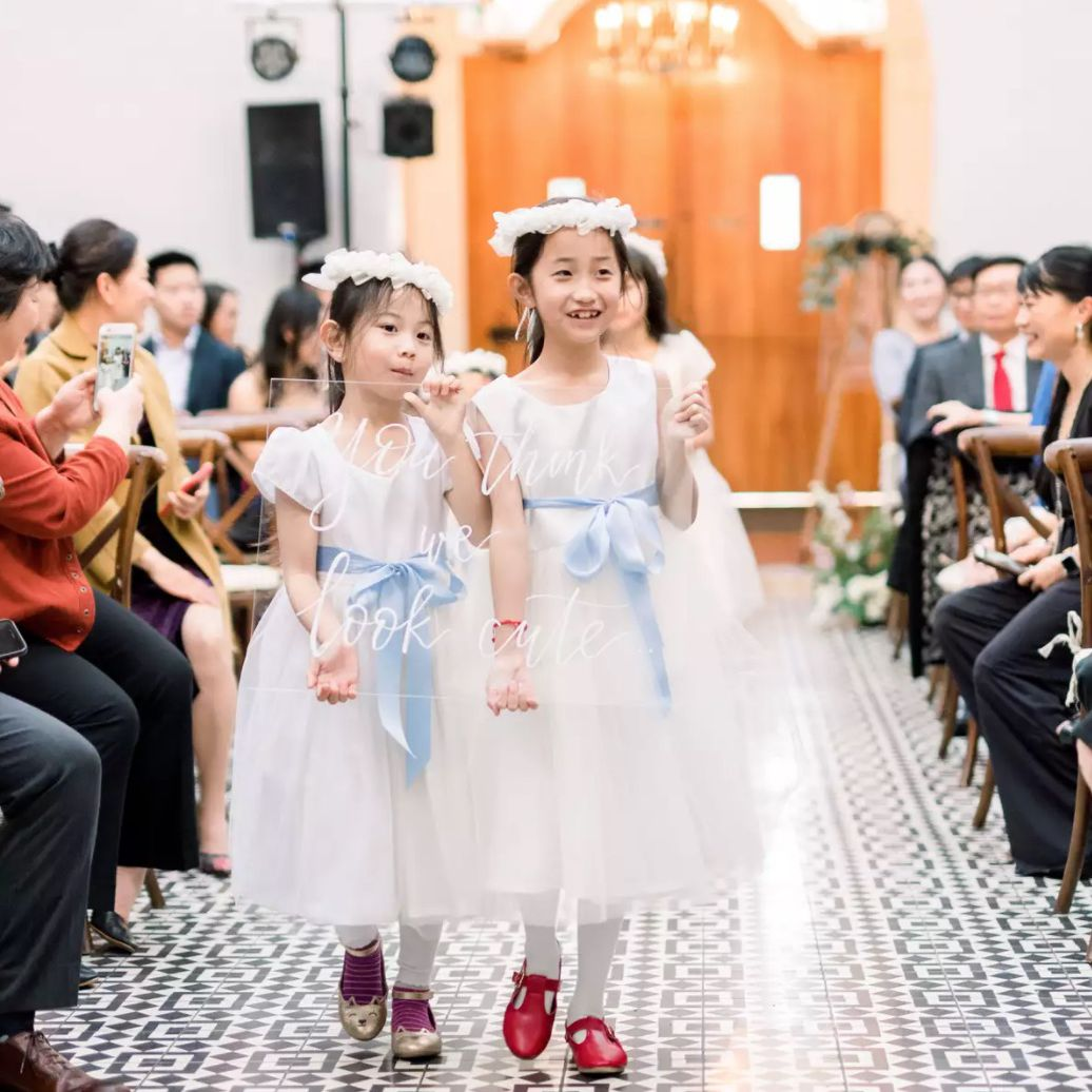 Flower girls walking down aisle with sign