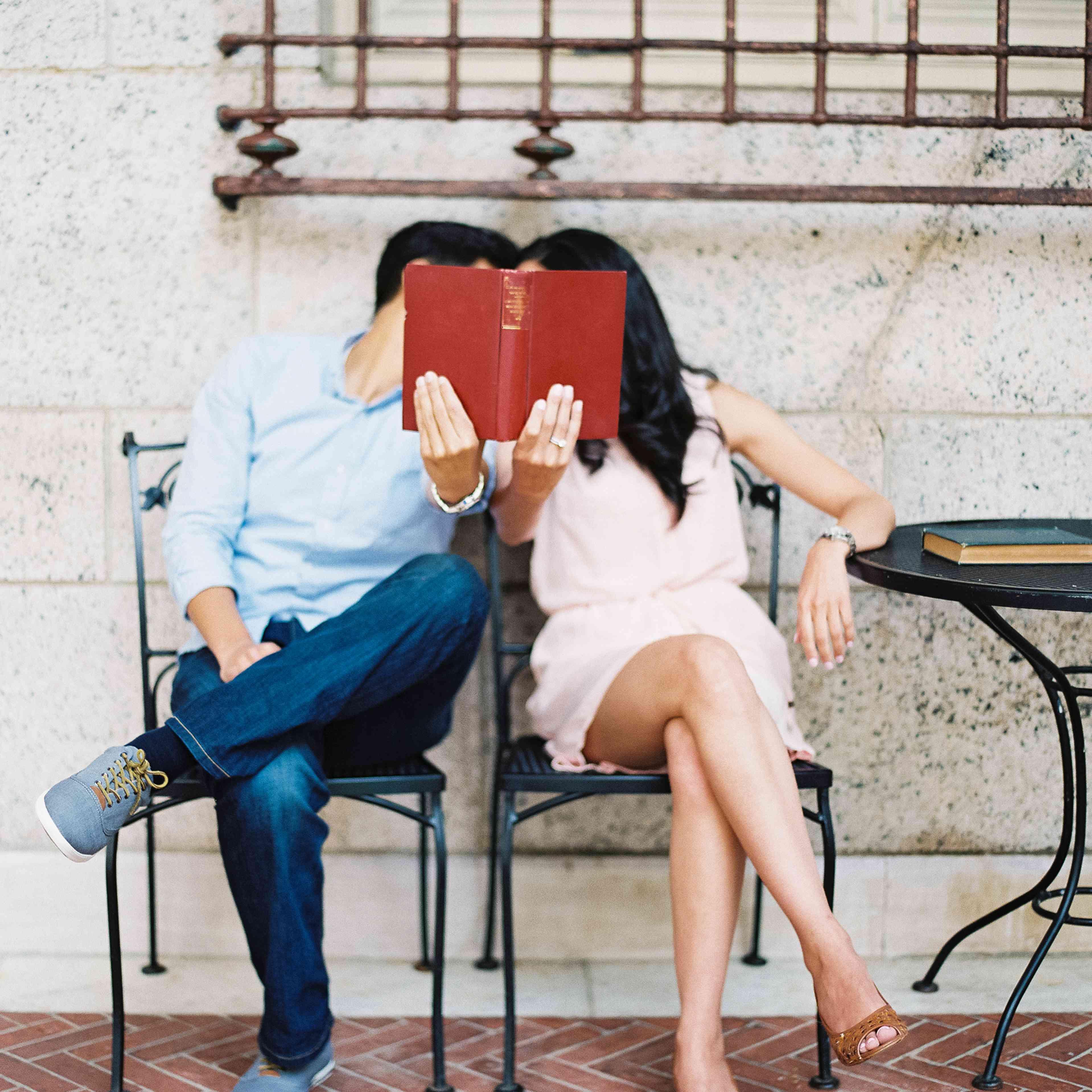 Couple hiding behind book