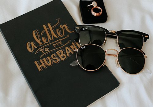 Love letter book for wedding with rings and sunglasses