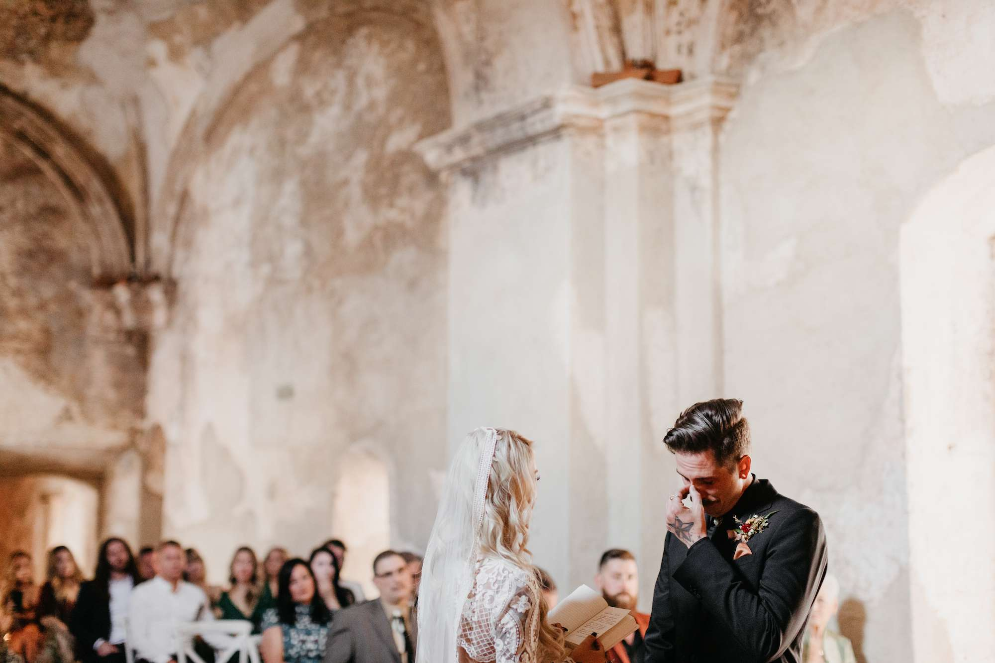 Groom wiping tears at wedding altar with bride