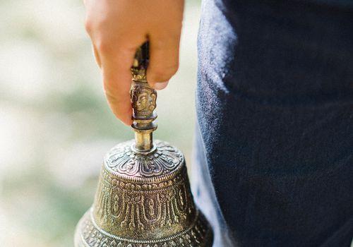 A boy holding a bell at a wedding.