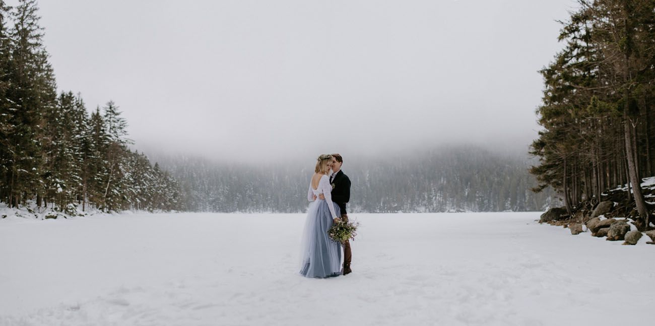 Bride and groom outside in a snowy clearing of a pine forest