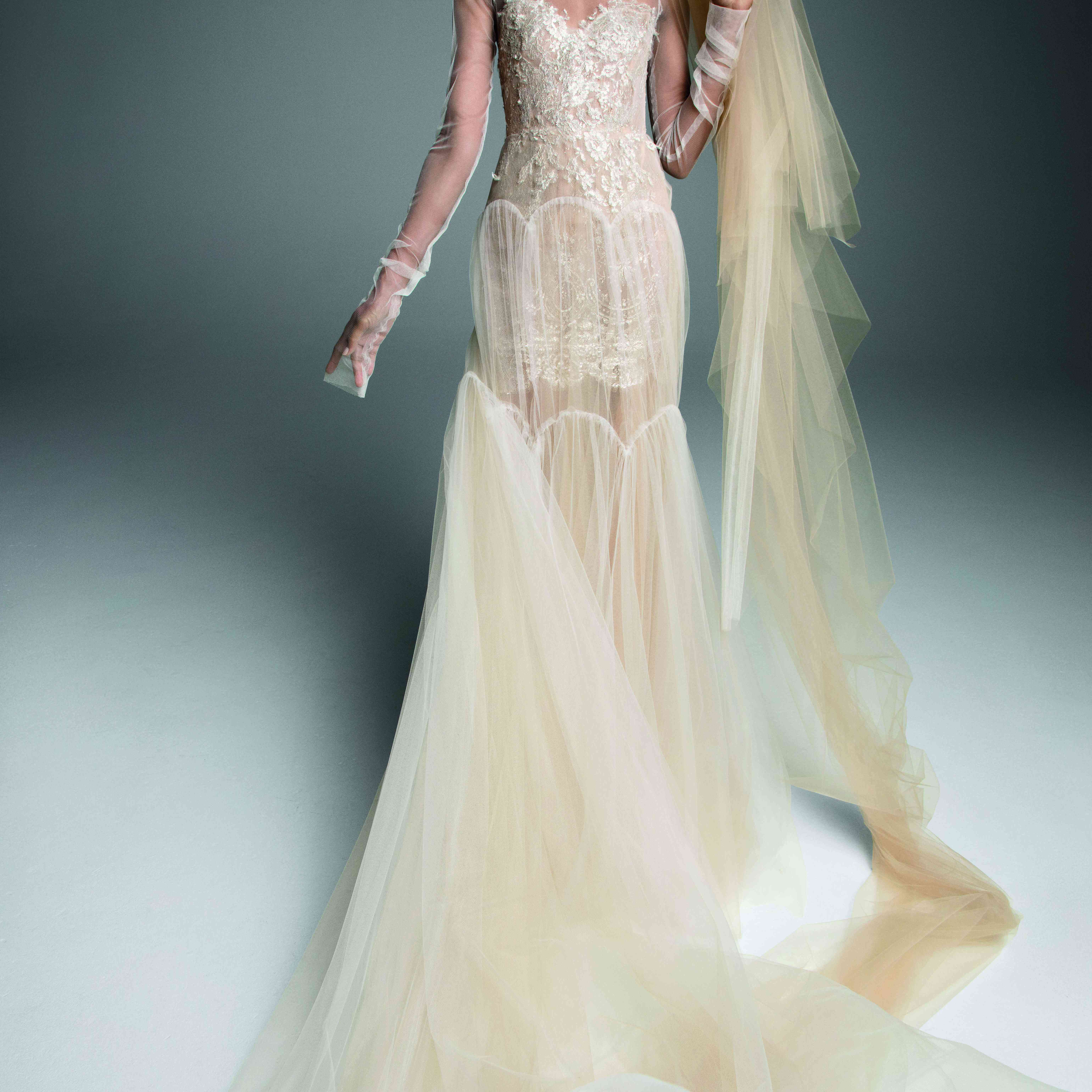 Model in ivory and nude tulle long-sleeve gown with a tiered skirt and lace accents on the bodice and neck