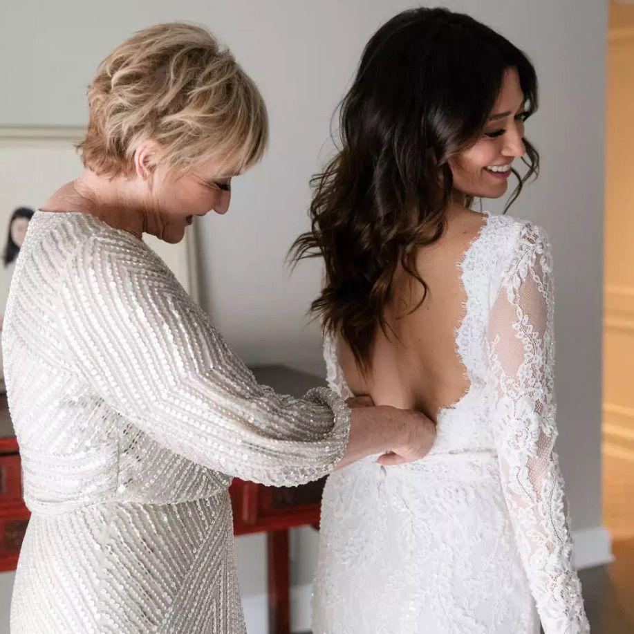 Mom zipping bride into dress