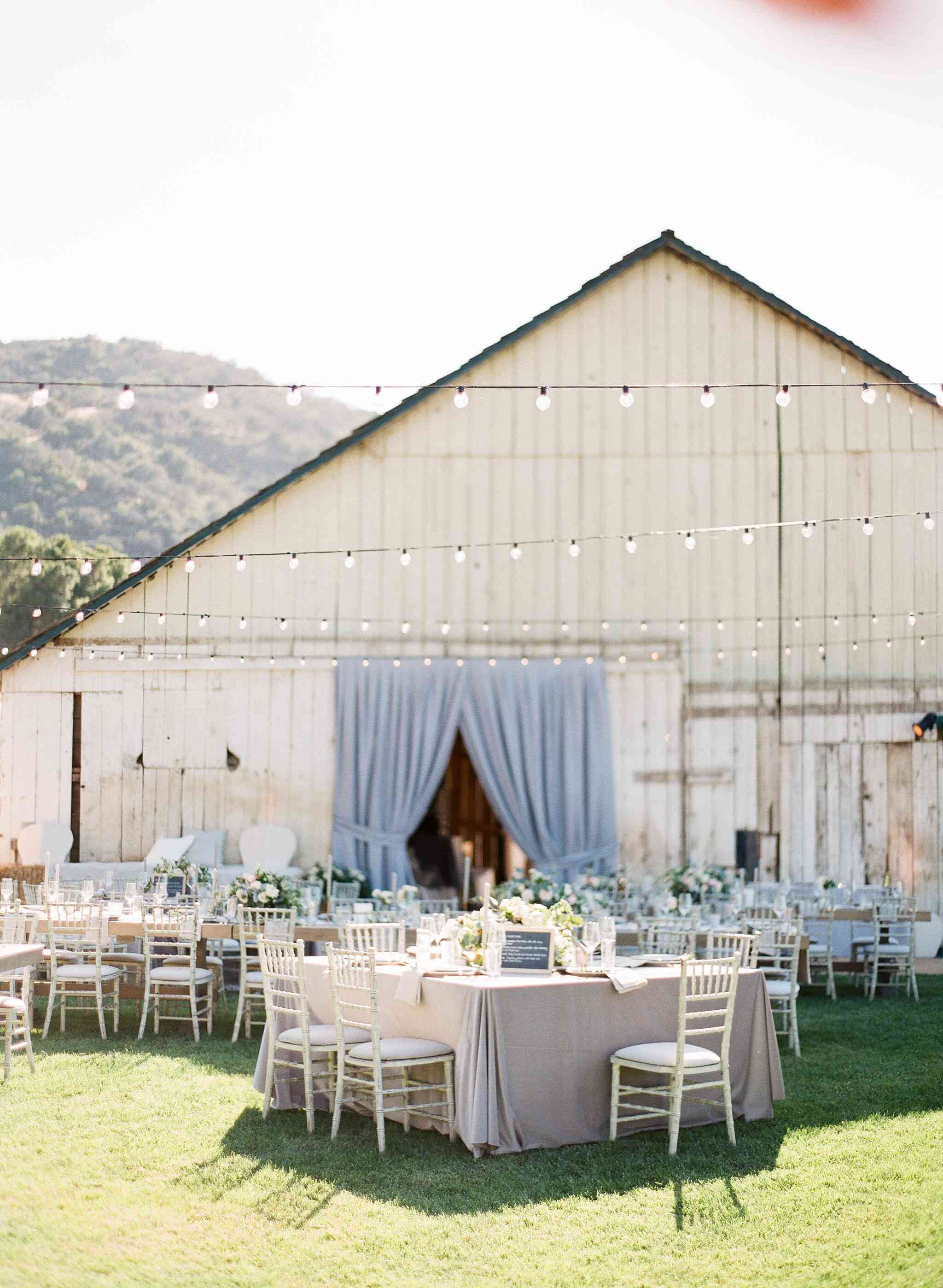 Tables set up in front of a barn-like home