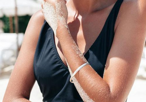 Woman at the beach with sand on her arm