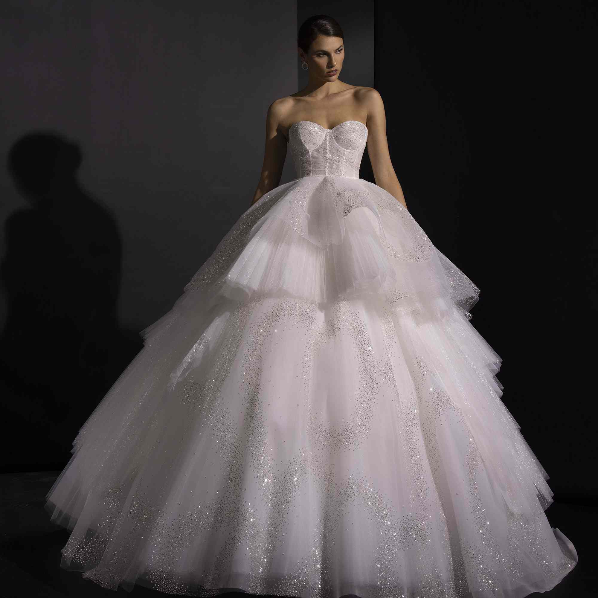 Model in strapless ballgown with voluminous tiered tulle skirt