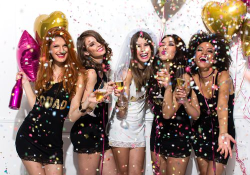 Young girlfriends celebrating bride night. Bride is wearing a veil and a T-shirt with the inscription ''BRIDE'', bridesmaids are wearing T-shirts with the inscription ''Squad''. Standing in front of a white wall, cheering with champagne and dancing. Confetti in the air.