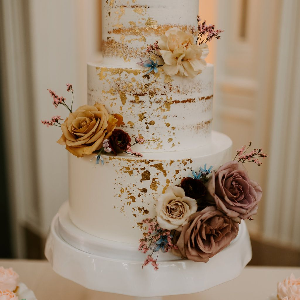 Three-tiered white wedding cake with gold and floral accents