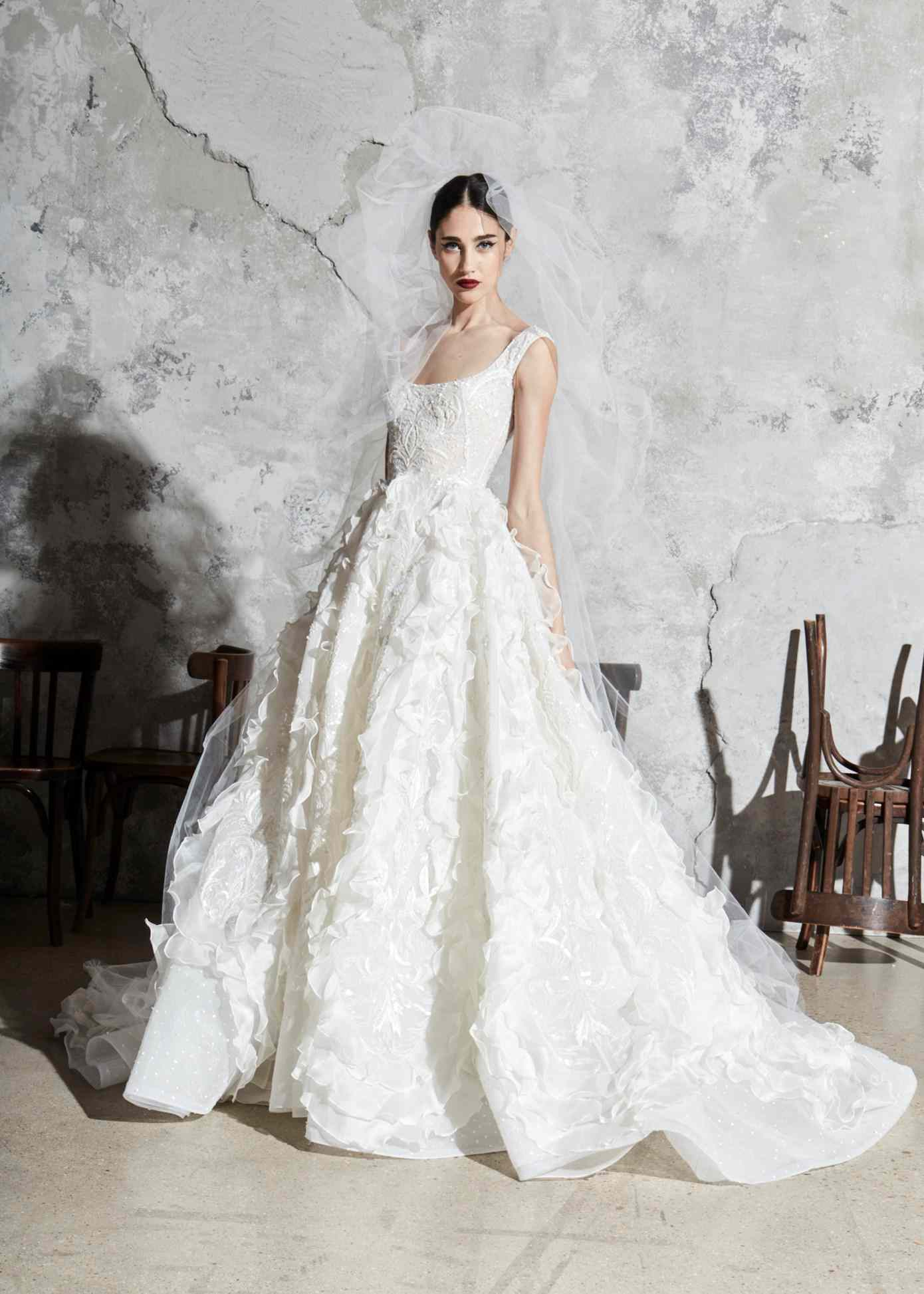 model in a sleeveless scoop-neck ballgown with an embroidered bodice and ruffled skirt