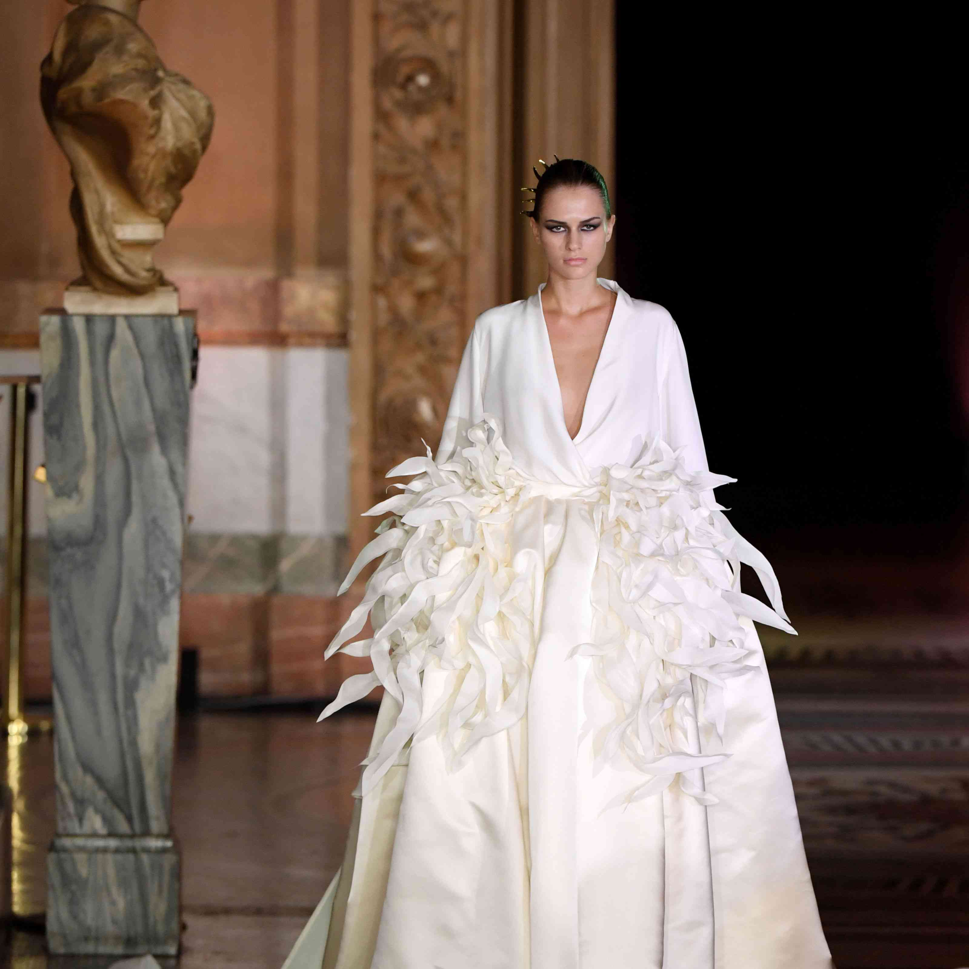 Model walking runway in long-sleeved gown with feathers