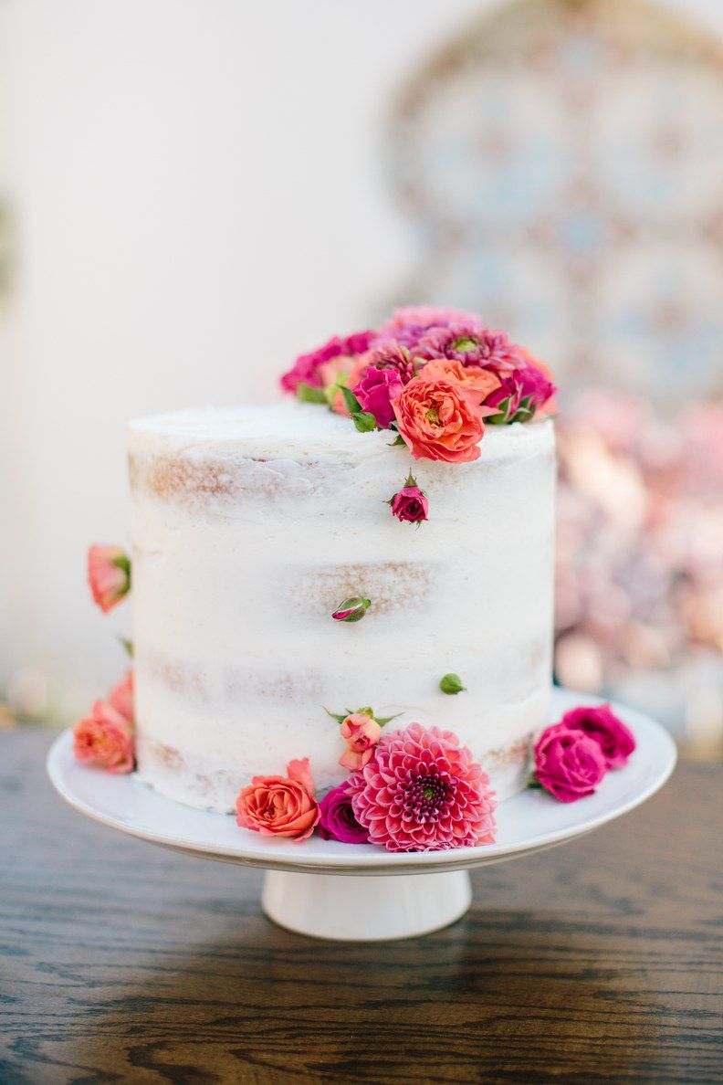 Simple semi-naked wedding cake with white frosting and pink floral decorations