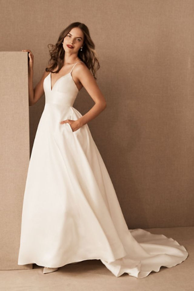 Model in thin-strap white wedding gown with pockets