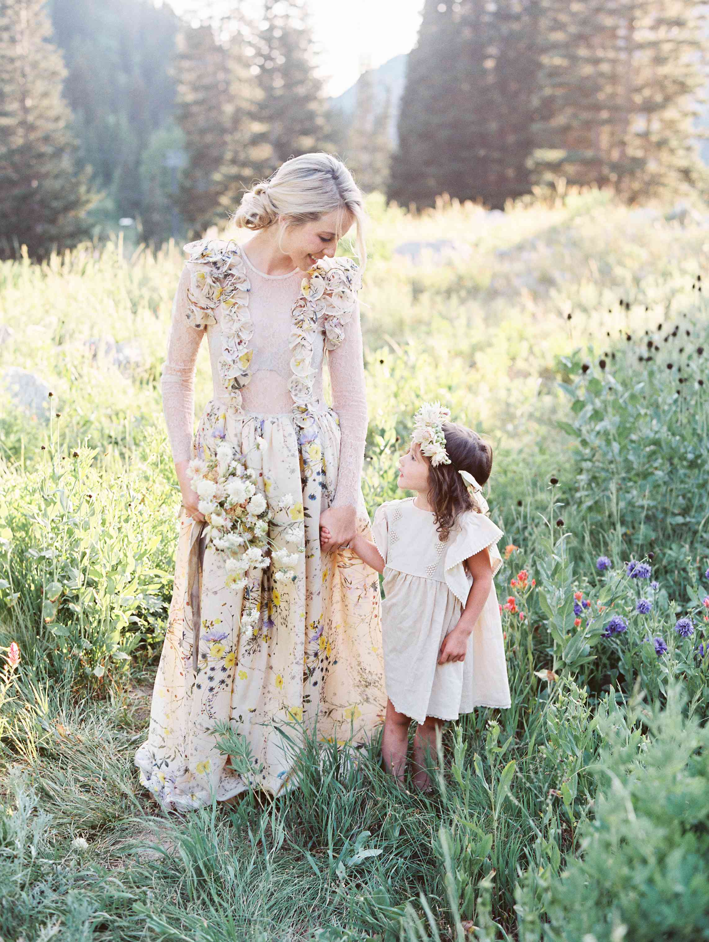 Bride in a floral printed dress holding flower girl's hand in a field of flowers