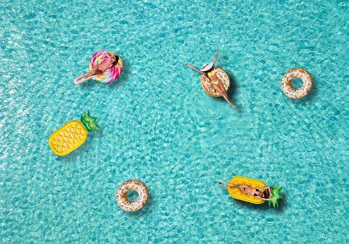 women on pool floats