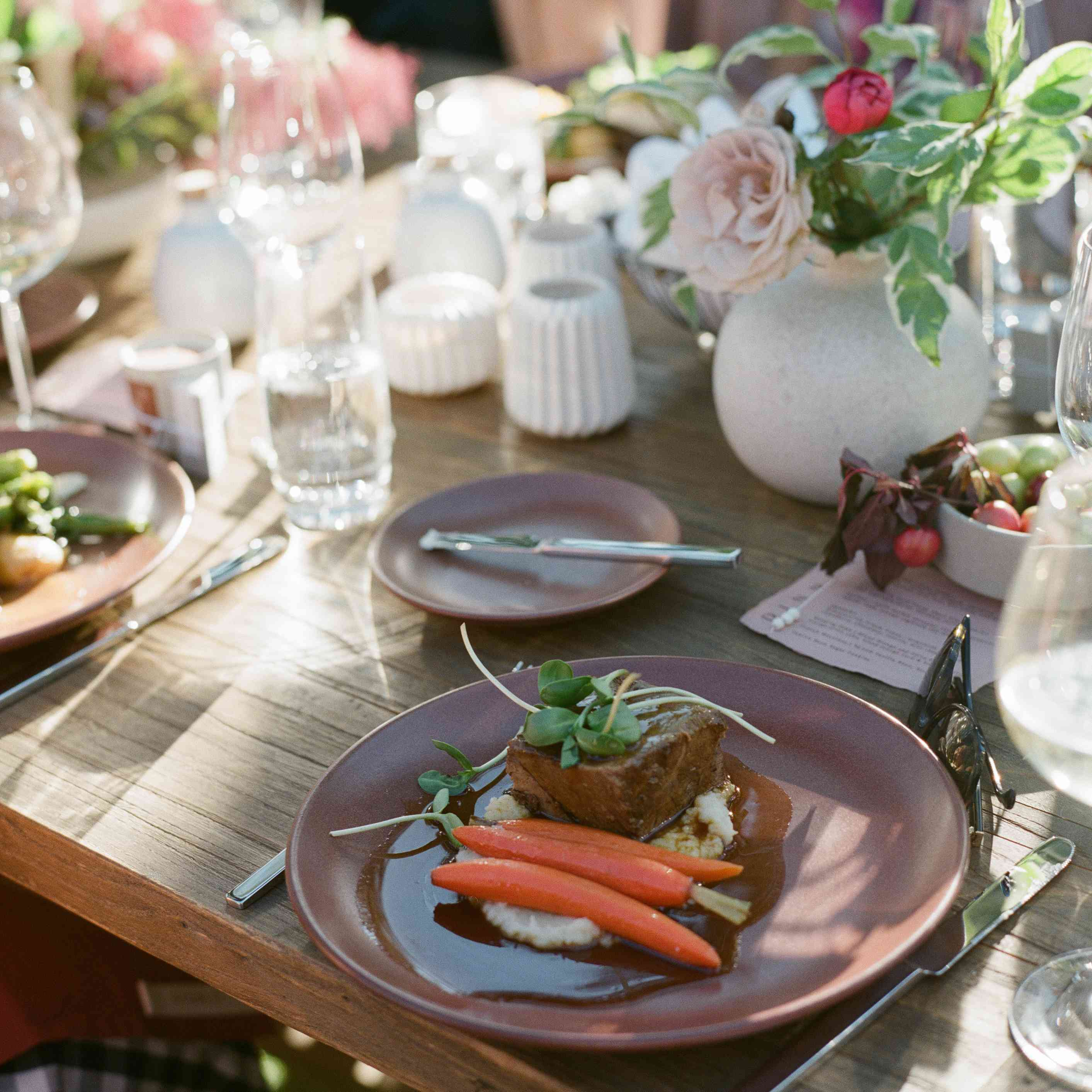 A plate of food with steak, carrots, and mashed potatoes at a wedding