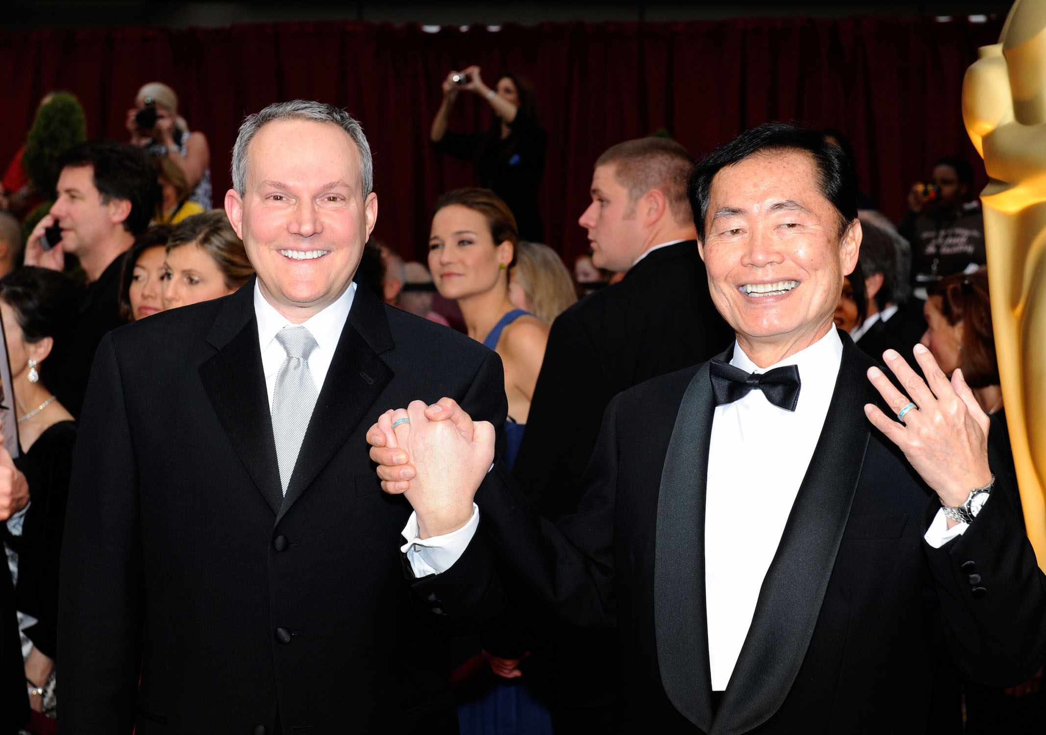 Brad Takei holds husband George Takei's hand on the Oscars red carpet as George flashes his ring