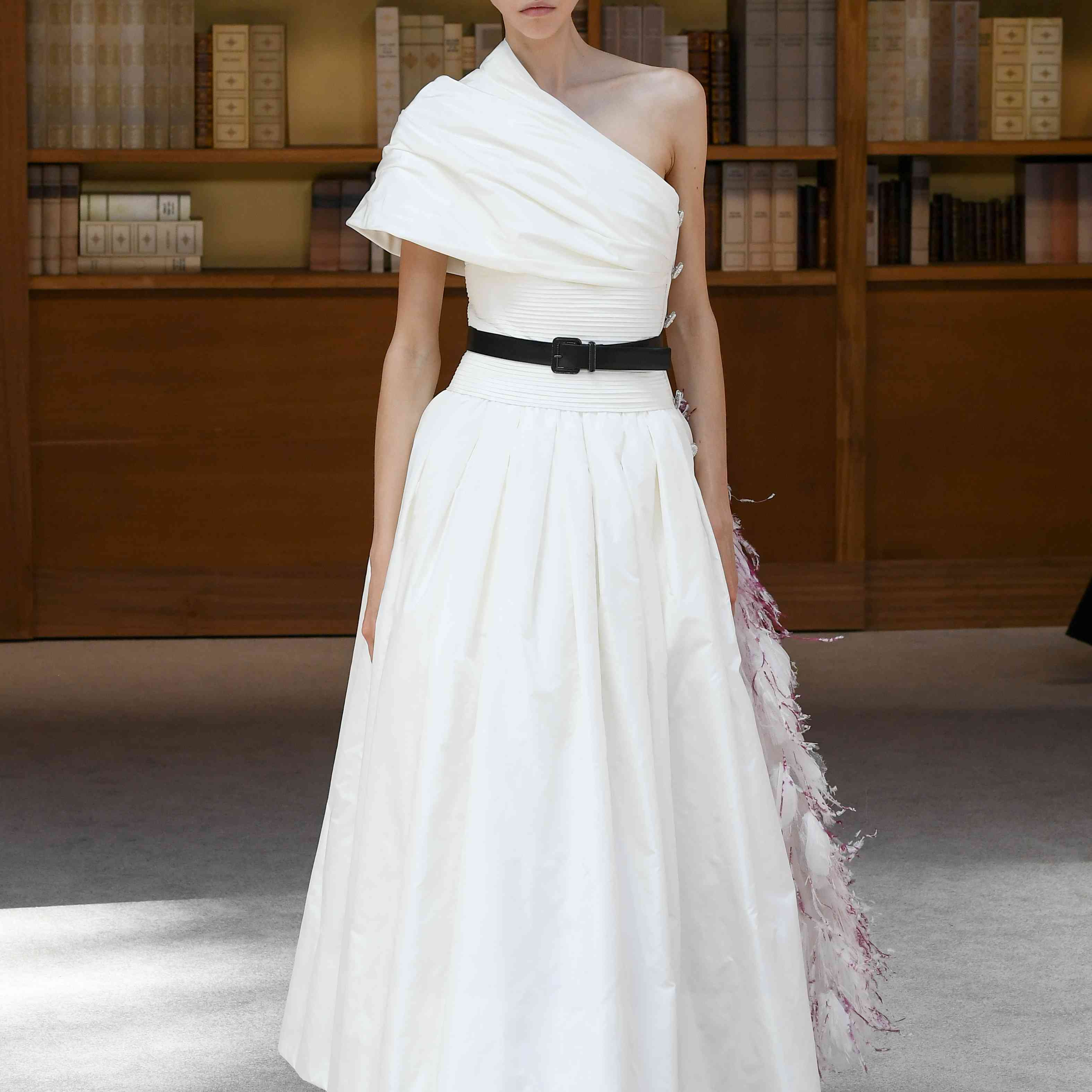 A model in a one-shoulder white dress with black belt