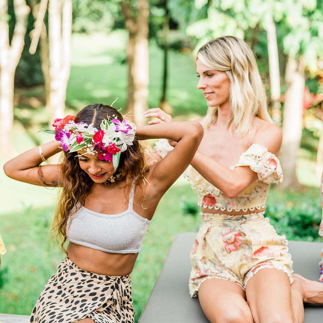woman helping friend put on flower crown